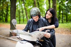 Image of young happy loving couple holding map outdoors near scooter. stock photos