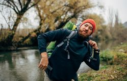 Image of young hiker male hiking in mountains with travel backpack. Traveler bearded man relaxing after mountaineering. Standing near to a river. Travel, people royalty free stock photography