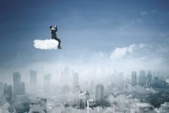 Young manager with binoculars on the cloud. Image of young male manager using binoculars above a city while sitting on the cloud Royalty Free Stock Photos