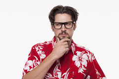 Image of a young man in Hawaiian shirt posing with hand on chin Royalty Free Stock Photos