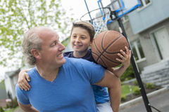 Image of young man and his son playing basketball royalty free stock images
