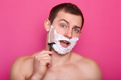 Image of young man posing with open mouth, shaving in bathroom and singing, keeps razor in hand, stands with naked shoulders,. Doing everyday procedures,  on royalty free stock photography
