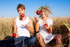 Image of young man and woman with apples on wheat field Stock Photos