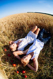 Image of young man and woman lying  on wheat field. Top view Royalty Free Stock Photo