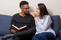 Image of young multicultural married couple sitting on couch sofa at home, attractive woman keeps hands on male`s shoulders, stock photos