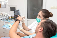 Image of young patient and dentist showing him x-ray radiography Royalty Free Stock Photos