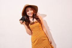 Image of young photographer woman  over beige background wall holding camera royalty free stock image