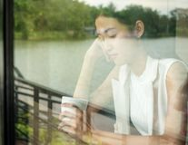 Image of young and pretty asia woman with cup of coffee and is thinking of someone.  stock photos