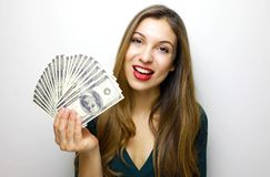 Image of young rich woman smiling with white teeth and holding lots of money in dollar currency isolated over white background stock image