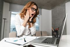 Shocked emotional business woman dressed in formal clothes shirt indoors using laptop computer stock photos