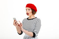 Young shocked woman chatting by mobile phone. Image of young shocked woman isolated over white background wall chatting by mobile phone. Looking aside stock photography
