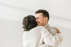 Image of young smiling guy embracing his girlfriend and looking through window Royalty Free Stock Photography