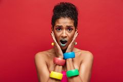 Image of young surprised mulatto woman being bright and stylish. Grabbing face wearing bracelets on arms over red background Stock Images
