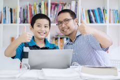 Young teacher showing thumbs up with his student. Image of young teacher showing thumbs up with his student while sitting in the classroom royalty free stock image