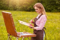 Image of young woman drawing picture on canvas, using sketchbook for drawing in nature, painter girl profile with brush and stock photo