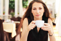 Image of young woman drinks coffee in cafe Stock Photography