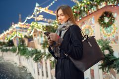 Image of young woman with phone in hands on winter walk in city stock photo