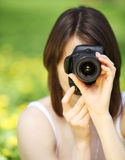 Image of young woman photographing in summer park Royalty Free Stock Images