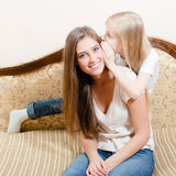 Image of young woman sitting on a couch and the girl child whispers something in her ear Stock Image