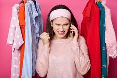 Image of young woman with unpleasant facial expression, being in shopping mall, talking on phone and clenching her fists with stock photography