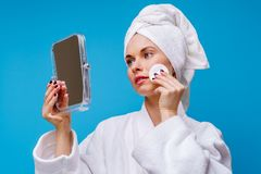Image of young woman in white coat and towel on her head with cotton pad and mirror in her hand. On empty blue background stock photography