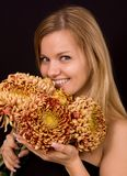 Image of a young woman with yellow chrysanthemums Royalty Free Stock Photo