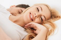 Young woman looking camera while her husband sleeping. Image of young women looking camera while her husband boyfriend lies in bed sleeping indoors at home Royalty Free Stock Photos