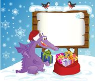 The image - for your message for winter holidays. Cute Dragon, symbol 2012 year, lays presents in a sack. After him a forest board is with the sheet of paper for Stock Images