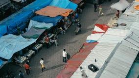 imagem aérea do zangão do mercado da cidade da manhã com as barracas coloridas que olham abaixo do close up quando povos que anda fotos de stock royalty free