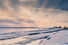 A imagem abstrata do por do sol no lago com o gelo de derretimento na mola adiantada Cores douradas, grama e pedras da hora Silho imagens de stock