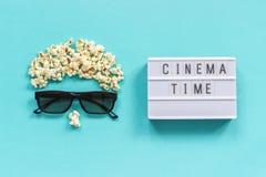 Imagem abstrata do tempo do cinema do texto da caixa do visor, dos vidros 3D, da pipoca e de luz no fundo de papel azul Filme do  fotografia de stock