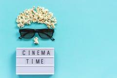 Imagem abstrata do tempo do cinema do texto da caixa do visor, dos vidros 3D, da pipoca e de luz no fundo de papel azul Filme do  foto de stock