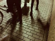 Imagem abstrata dos povos que andam e que dão um ciclo em um pavimento de pedra imagem de stock