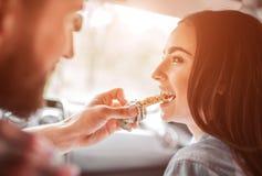 Imagem agradável do indivíduo que alimenta sua amiga com barra de chocolate Está mordendo uma parte e um sorriso A menina está ol imagem de stock