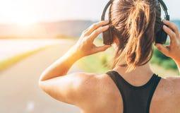 Imagem ascendente próxima do adolescente que ajusta fones de ouvido sem fio antes de começar movimentar-se e de escutar a música imagens de stock