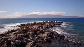 A imagem atrativa de penhascos bonitos no oceano e no estouro acena perto deles sob o céu azul na ilha maui filme