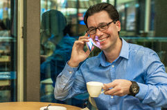 Imagem autêntica de um homem de negócios que trabalha em um café Equipe a fala no telefone celular em uma cafetaria fotografia de stock royalty free