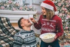Imagem bonita de suportes e de alimentar da jovem mulher seu noivo Guarda a parte de pipoca acima de sua boca O indivíduo mantém- fotografia de stock