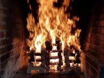 Imagem bonita do fogo móvel em uma fogueira feita com as pranchas de madeira na grade na chaminé do tijolo imagem de stock royalty free