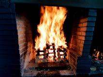 Imagem bonita do fogo móvel em uma fogueira feita com as pranchas de madeira na grade na chaminé do tijolo imagens de stock royalty free