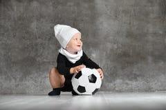 Imagem bonito do bebê que guarda uma bola de futebol fotografia de stock