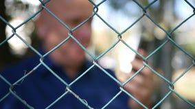 Imagem borrada com um homem feliz que Texting usando o telefone celular de uma área da proteção filme