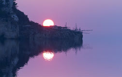 Imagem borrada das reflexões no mar no por do sol com foco macio do sol e do trabocco Foto de Stock