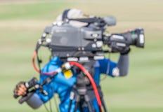 A imagem borrada de um homem está gravando VDO durante o competiam do golfe Foto de Stock