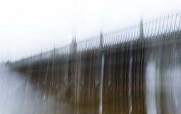 Imagem borrada de uma ponte antiga longa com uma cerca do ferro forjado na névoa, feita com uma exposição longa O conceito de um  Fotos de Stock Royalty Free