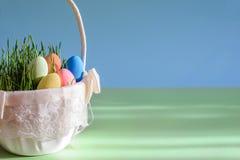 Imagem brilhante bonita com os ovos da páscoa na cesta no fundo azul esverdeado com espaço da cópia Fotografia de Stock