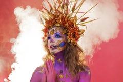 Imagem brilhante de Dia das Bruxas, estilo mexicano com os crânios do açúcar na cara Pele cor-de-rosa brilhante da mulher bonita  imagem de stock
