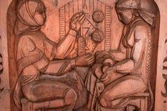 Imagem cinzelada na madeira com weave das mulheres Imagem de Stock Royalty Free