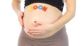 Imagem colhida da mulher gravida com vinda logo sinal em sua posição da barriga, branco, close up filme