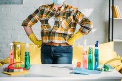 imagem colhida da mulher que está a tabela próxima com fontes de limpeza em casa fotos de stock royalty free